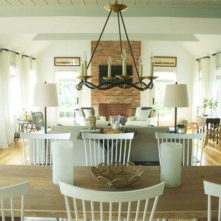 Immagine di un soggiorno costiero aperto con pareti bianche, parquet chiaro, camino classico, cornice del camino in mattoni e TV a parete