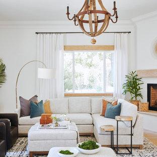 Foto di un grande soggiorno mediterraneo con pareti bianche, pavimento in ardesia, camino ad angolo, cornice del camino in intonaco e sala formale