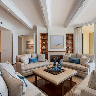 Example of a beach style medium tone wood floor living room design in Miami with beige walls and a standard fireplace