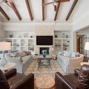 Imagen de salón para visitas abierto, costero, grande, con paredes blancas, suelo de madera en tonos medios, chimenea tradicional, marco de chimenea de baldosas y/o azulejos y televisor colgado en la pared