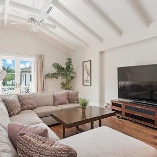 マイアミの中サイズのビーチスタイルのおしゃれな独立型リビング (フォーマル、白い壁、無垢フローリング、据え置き型テレビ、茶色い床) の写真