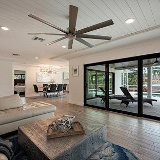 他の地域の小さいビーチスタイルのおしゃれなLDK (フォーマル、白い壁、セラミックタイルの床、据え置き型テレビ、茶色い床) の写真