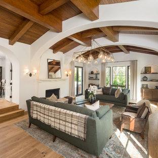 Diseño de salón para visitas cerrado, mediterráneo, sin televisor, con paredes blancas, suelo de madera clara y chimenea tradicional