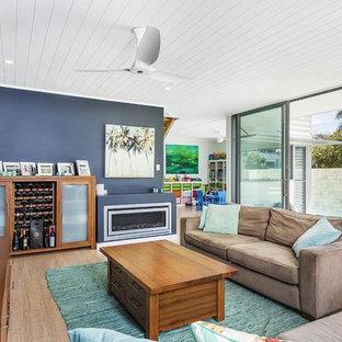 シドニーの広いビーチスタイルのおしゃれなLDK (黒い壁、竹フローリング、標準型暖炉、漆喰の暖炉まわり、据え置き型テレビ) の写真
