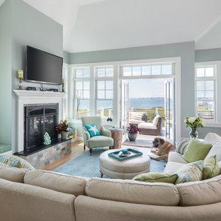 プロビデンスの中サイズのビーチスタイルのおしゃれなLDK (青い壁、淡色無垢フローリング、標準型暖炉、木材の暖炉まわり、壁掛け型テレビ) の写真