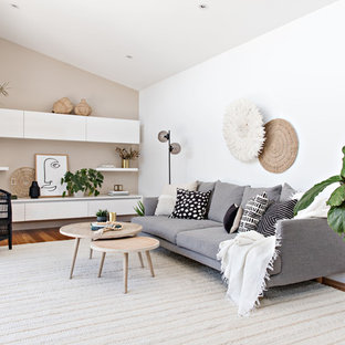 Inspiration for a mid-sized beach style open concept living room in Sydney with no fireplace, white walls, medium hardwood floors and brown floor.