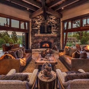 Imagen de salón abierto, rústico, con paredes marrones, suelo de madera oscura, chimenea de esquina, marco de chimenea de piedra y televisor colgado en la pared