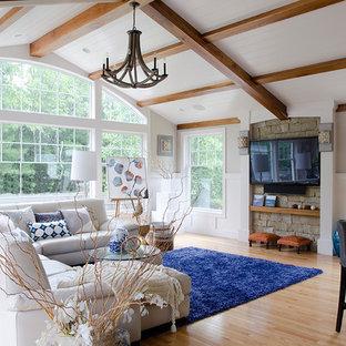 Idée de décoration pour un salon marin ouvert et de taille moyenne avec un mur gris, un sol en bois clair, un téléviseur fixé au mur, une salle de réception et un sol beige.