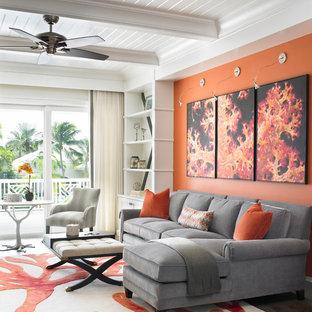 Imagen de salón abierto, tradicional renovado, con parades naranjas y suelo de madera oscura