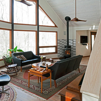 Mid-sized danish open concept light wood floor living room photo in DC Metro with white walls, a wood stove and a tile fireplace