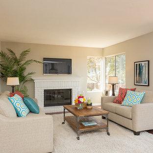 サンフランシスコの中サイズのコンテンポラリースタイルのおしゃれなLDK (ベージュの壁、濃色無垢フローリング、標準型暖炉、レンガの暖炉まわり、壁掛け型テレビ) の写真