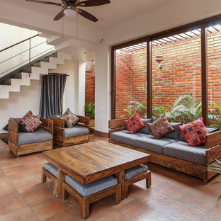 World-inspired formal living room in Bengaluru with white walls, brown floors and brick flooring.
