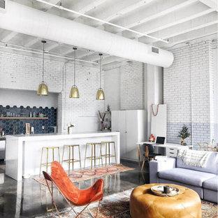Foto di un grande soggiorno industriale aperto con pareti bianche e pavimento in cemento