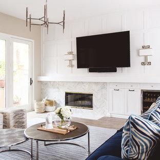 サンディエゴのミッドセンチュリースタイルのおしゃれな独立型リビング (ベージュの壁、淡色無垢フローリング、標準型暖炉、石材の暖炉まわり、壁掛け型テレビ) の写真