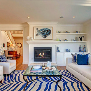Inspiration for a coastal medium tone wood floor living room remodel in Los Angeles with white walls and a standard fireplace