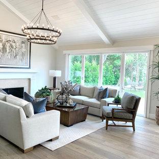Großes, Offenes Country Wohnzimmer mit beiger Wandfarbe, braunem Holzboden, Kamin, Kaminumrandung aus Stein, beigem Boden und Holzdielendecke in Orange County