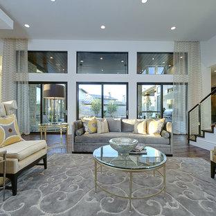 Foto di un grande soggiorno classico aperto con pareti bianche, angolo bar, pavimento in legno massello medio, nessun camino, nessuna TV e pavimento marrone