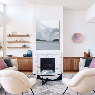 This is an example of a contemporary open concept living room in Sydney with white walls, medium hardwood floors, a standard fireplace and brown floor.
