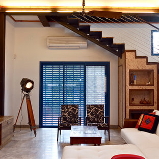 Ejemplo de salón bohemio con paredes beige, suelo de cemento y televisor colgado en la pared