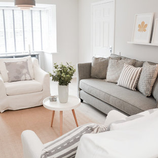 Photo of a scandinavian living room in Hampshire with white walls, light hardwood flooring, a freestanding tv and beige floors.