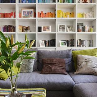 Ejemplo de salón con rincón musical abierto, actual, pequeño, con paredes blancas, suelo de madera clara, televisor colgado en la pared y suelo gris