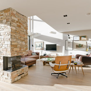 Scandi open plan living room in Other with white walls, light hardwood flooring, a stone fireplace surround and a wall mounted tv.
