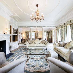 Ejemplo de salón para visitas abierto, tradicional, de tamaño medio, con parades naranjas, suelo de madera clara, chimenea tradicional y pared multimedia