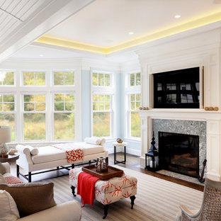 ボストンの大きいビーチスタイルのおしゃれなLDK (濃色無垢フローリング、標準型暖炉、石材の暖炉まわり、内蔵型テレビ) の写真