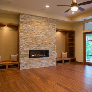 Imagen de salón para visitas abierto, contemporáneo, grande, sin televisor, con paredes beige, suelo de bambú, chimenea lineal, marco de chimenea de piedra y suelo marrón
