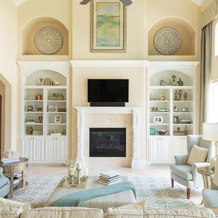 Inspiration for a large timeless open concept travertine floor living room remodel in Houston with yellow walls, a standard fireplace, a tile fireplace and a wall-mounted tv