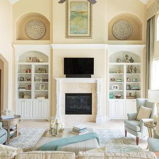 Diseño de salón abierto, clásico, grande, con paredes amarillas, suelo de travertino, chimenea tradicional, marco de chimenea de baldosas y/o azulejos y televisor colgado en la pared