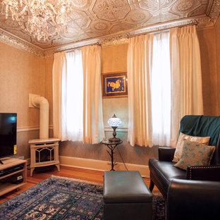 Imagen de biblioteca en casa cerrada, tradicional, pequeña, con paredes beige, suelo de madera en tonos medios, estufa de leña, marco de chimenea de metal, televisor independiente y suelo azul