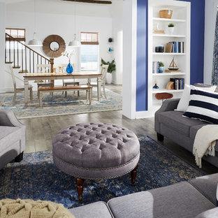 Aménagement d'un salon bord de mer de taille moyenne avec un sol en bois clair, aucune cheminée, aucun téléviseur, un sol gris, une salle de réception et un mur bleu.