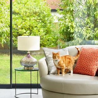 Foto di un soggiorno contemporaneo aperto con pareti bianche, pavimento in pietra calcarea e TV a parete