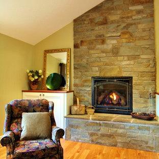 ポートランドの広いトラディショナルスタイルのおしゃれなLDK (ベージュの壁、無垢フローリング、標準型暖炉、石材の暖炉まわり、壁掛け型テレビ) の写真