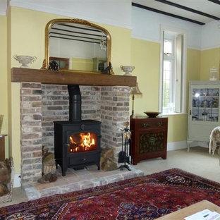 Foto di un soggiorno shabby-chic style con stufa a legna e cornice del camino in mattoni