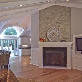 シカゴの広いトラディショナルスタイルのおしゃれなLDK (グレーの壁、壁掛け型テレビ、フォーマル、淡色無垢フローリング、吊り下げ式暖炉、石材の暖炉まわり、茶色い床) の写真