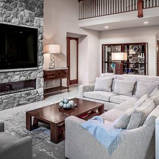 Klassisk inredning av ett mycket stort allrum med öppen planlösning, med en hemmabar, en väggmonterad TV, grå väggar, en bred öppen spis och en spiselkrans i sten