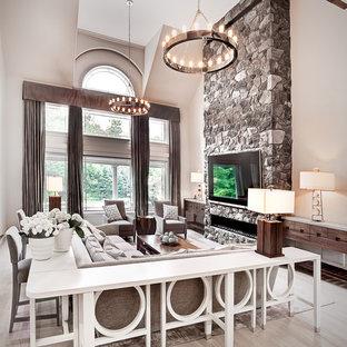 Foto på ett mycket stort vintage allrum med öppen planlösning, med grå väggar, ljust trägolv, en bred öppen spis, en spiselkrans i sten och en väggmonterad TV