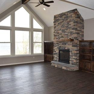 ミネアポリスの中サイズのラスティックスタイルのおしゃれなLDK (グレーの壁、濃色無垢フローリング、標準型暖炉、石材の暖炉まわり、茶色い床) の写真