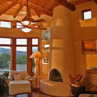 アルバカーキの小さいサンタフェスタイルのおしゃれな独立型リビング (黄色い壁、コンクリートの床、標準型暖炉、漆喰の暖炉まわり) の写真