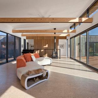 Idee per un soggiorno etnico di medie dimensioni e aperto con sala della musica, pareti bianche, pavimento in sughero, stufa a legna, cornice del camino in metallo, nessuna TV e pavimento beige