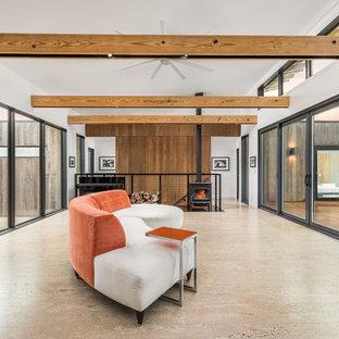 Ispirazione per un soggiorno minimalista di medie dimensioni e aperto con pareti bianche, pavimento in sughero, stufa a legna, cornice del camino in metallo e pavimento beige