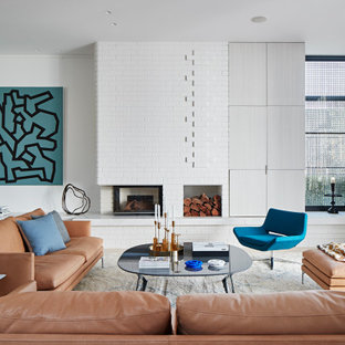 This is an example of a large contemporary formal living room in Melbourne with white walls, light hardwood floors, a standard fireplace, a brick fireplace surround, no tv and beige floor.