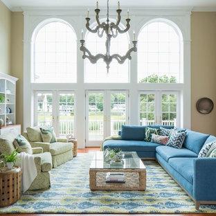 Immagine di un soggiorno bohémian di medie dimensioni e stile loft con libreria, pareti beige, parquet chiaro, camino bifacciale, cornice del camino in legno e TV a parete
