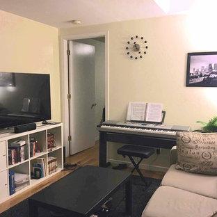Idee per un piccolo soggiorno minimalista chiuso con pareti beige, pavimento in bambù e TV autoportante