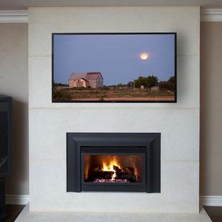 Diseño de salón para visitas cerrado, contemporáneo, pequeño, con paredes beige, marco de chimenea de piedra, suelo marrón, suelo de madera en tonos medios, chimenea tradicional y televisor colgado en la pared