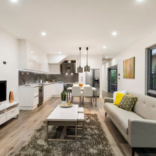 Photo of a contemporary open concept living room in Melbourne with white walls, light hardwood floors and a freestanding tv.