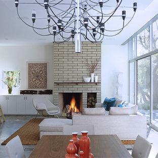 Idee per un soggiorno moderno di medie dimensioni e aperto con libreria, pareti bianche, pavimento in cemento, camino classico, cornice del camino piastrellata, nessuna TV e pavimento grigio