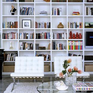На фото: открытые гостиные комнаты среднего размера в стиле модернизм с бетонным полом, библиотекой, белыми стенами, стандартным камином, фасадом камина из плитки и серым полом без ТВ